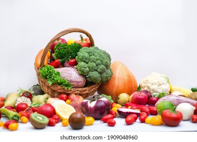Assorted organic vegetables and fruits in wicker basket isolated on white background. Healthy food.