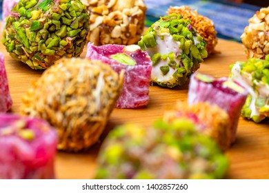 Assorted oriental sweets on a wooden board. Assorted traditional Turkish Delight (lokum). Lokum with different nuts, stuffing, pistachios and peanuts