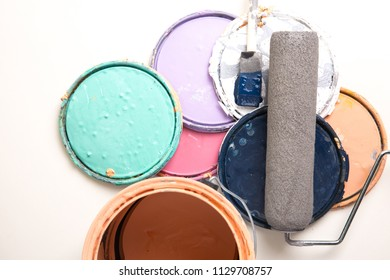 Assorted Paint Can Lids Paint Can paint roller and brush on a white background