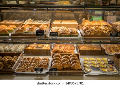 Assorted pastry and bread arranged on tray at bakery shop.