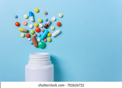 Assorted pharmaceutical medicine pills, tablets and capsules and bottle on blue background. Copy space for text