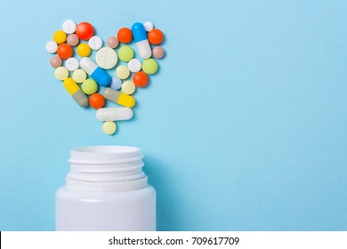 Assorted pharmaceutical medicine pills, tablets and capsules for the treatment of heart disease. Heart shape and bottle of pills. Copy space for text