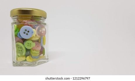 Assorted plastic buttons in a glass jar.