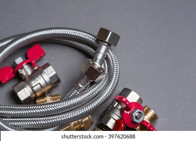 Assorted plumbing fittings and hose on grey surface