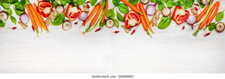 Assorted raw organic vegetables and ingredients for Healthy cooking on white wooden background, top view, banner. Vegetarian and diet food concept.