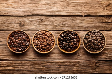 Assorted raw and roasted coffee beans in small individual containers on a rustic, weathered textured driftwood background, overhead view with copyspace