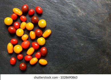 Assorted red, dark, yellow and orange small cherry tomatoes on slate