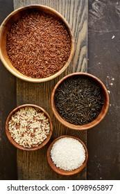 Assorted rice on cutting board. Jasmine , Brown , Red , Black rice (Zizania)