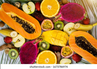 Assorted ripe juicy fresh tropical summer seasonal fruits on white background. Vacation, healthy food, dieting, summer concept. Sliced fruits on table. Top view.