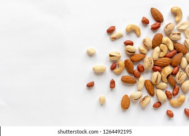 Assorted roasted and raw nuts scattered on white with almonds, peanuts, groundnuts, pistachios and cashews viewed in a flat lay still life from above with copy space