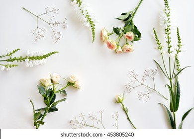 Assorted roses heads on white background. Flowers and leaves scattered on a table, overhead view wallpaper. Flat lay, top view.