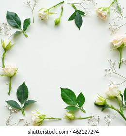 Assorted roses heads on white background. Flowers and leaves scattered on a table, overhead view wallpaper. Flat lay, top view. Nice border.