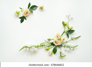Assorted roses heads on white background. Flowers and leaves scattered on a table, overhead view wallpaper. Flat lay, top view. Nice border. Decoration elements.