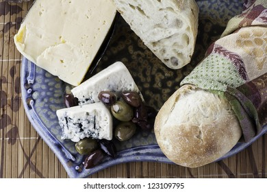 Assorted rustic bread with assorted olives and cheeses from a top down view
