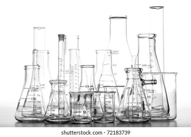 Assorted science laboratory glassware chemistry equipment featuring glass beakers with graduated scientific cylinders and conical Erlenmeyer flasks in a science research lab over white