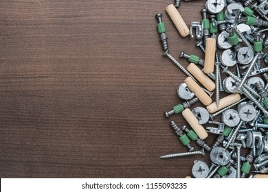 assorted screws for furniture assembly on the wooden table with copy space