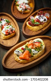 assorted set of bruschetta with salmon avocado cheese with herbs and tuna on a wooden plate on a black wooden menu background close up