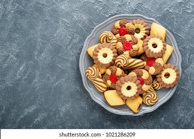 Assorted shortbread cookie on a plate on a gray background.top view.