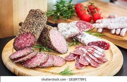 Assorted sliced italian pork salami on wooden plate