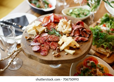Assorted slices of sausage, ham, salami, and cheese on a wooden board platter in an italian restaurant