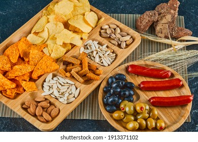 Assorted snacks, a plate of sausages, caviar, and olives on a wooden table