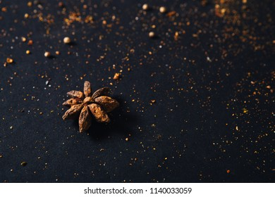 Assorted spices with empty space for text on dark black background. Seasonings for food. Curry, paprika, pepper, cardamom, cloves, turmeric, anise. Top view. Close-up.