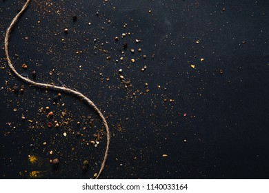 Assorted spices on dark black background. Seasonings for food. Curry, paprika, pepper, cardamom, cloves, turmeric. Empty space for text. Top view. Close-up.