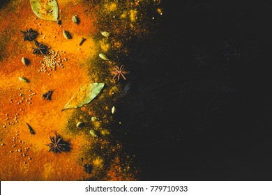 Assorted spices on dark black background. Seasonings for food. Space for text. Curry, paprika, pepper, cardamom, anise, cloves, bay leaf, turmeric. Top view. Close-up. Spices concept. Copy space