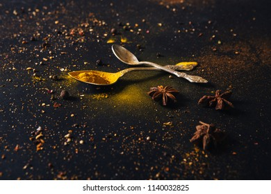 Assorted spices in spoons with empty space for text on dark black background. Seasonings for food. Curry, paprika, pepper, cardamom, anise, cloves, turmeric. Close-up.