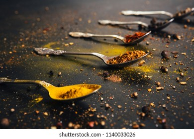 Assorted spices in spoons with empty space for text on dark black background. Seasonings for food. Curry, paprika, pepper, cardamom, cloves, turmeric. Close-up.