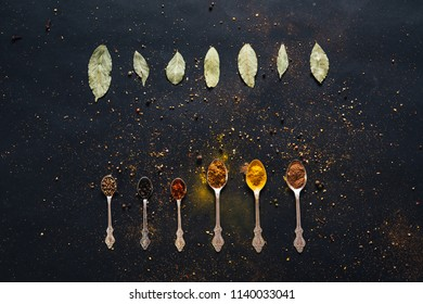 Assorted spices in spoons with empty space for text on dark black background. Seasonings for food. Curry, paprika, pepper, cardamom, cloves, turmeric, bay leaf. Top view. Close-up.
