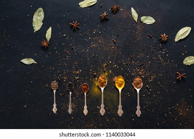 Assorted spices in spoons with empty space for text on dark black background. Seasonings for food. Curry, paprika, pepper, cardamom, cloves, turmeric, anise, bay leaf. Top view. Close-up.