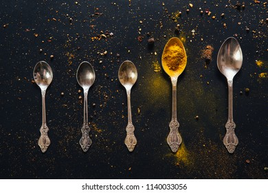 Assorted spices in spoons with empty space for text on dark black background. Seasonings for food. Curry, paprika, pepper, cardamom, cloves, turmeric. Top view. Close-up.
