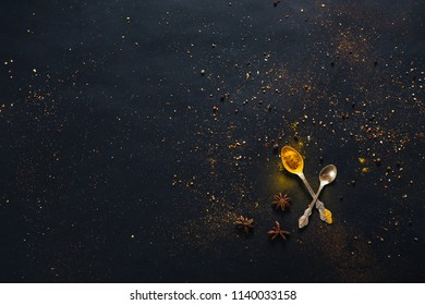 Assorted spices in spoons with empty space for text on dark black background. Seasonings for food. Curry, paprika, pepper, cardamom, anise, cloves, turmeric. Top view. Close-up.