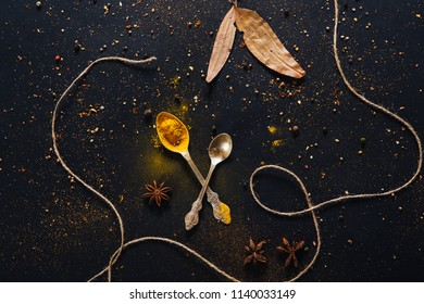 Assorted spices in spoons on dark black background. Seasonings for food. Curry, paprika, pepper, cardamom, anise, cloves, bay leaf, turmeric. Top view. Close-up.