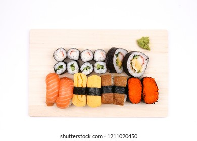 Assorted sushi on wooden board, white background