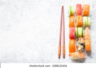 Assorted sushi set on white concrete background. Japanese sushi, chopsticks. Space for text. Top view. Sushi nigiri. Japanese dinner/lunch. Different sushi mixed. Japanese food concept. Food frame