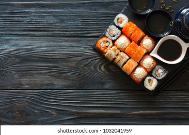 Assorted sushi and tea set served on a black wood table. Top view. Copy space