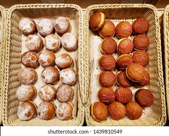 Assorted sweet donuts,  glazed and iced and powdered pastries in baskets in bakery shop