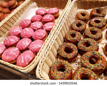 Assorted sweet donuts,  glazed pastries with sprinkles in basket in bakery shop