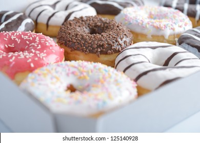 Assorted sweet donuts in a paper box. Shallow DOF