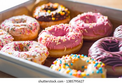 Assorted sweet donuts in a paper box.