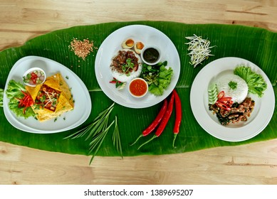 Assorted Thai street food on banana leaf presentation with spice. Padthai omelette egg, stewed pork leg over rice and , Thai spicy basil chicken over rice with chilli , scallion , crushed peanut.