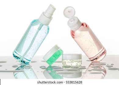 assorted toiletries and water droplets on white background
