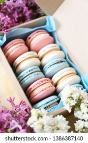 Assorted traditional french macarons sweets of different color and taste, two rows in present box with lilac flowerings decoration. Background, close up, copy space, top view.