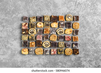 Assorted traditional turkish delight Rahat lokum on gray stone background. Rahat Lukum (lokum) sprinkled with coconut, sugar and sesame. Top view from above and copy space.