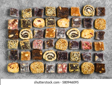 Assorted traditional turkish delight Rahat lokum on gray stone background. Rahat Lukum (lokum) sprinkled with coconut, sugar and sesame. Top view, flat lay.