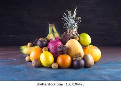 Assorted tropical fruits, orange,Ananas or pineapple, lime,mango, dragon fruit, orange, banan, rambutan and lichi on dark background. Copy space