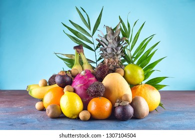 Assorted tropical fruits, orange,Ananas or pineapple, lime,mango, dragon fruit, orange, banan, rambutan and lichi on blue background.. Copy space