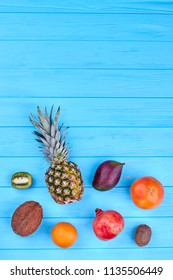 Assorted tropical fruits, top view. Set of exotic fruits over blue wooden background with copy space. Healthy and nutritious fruits.